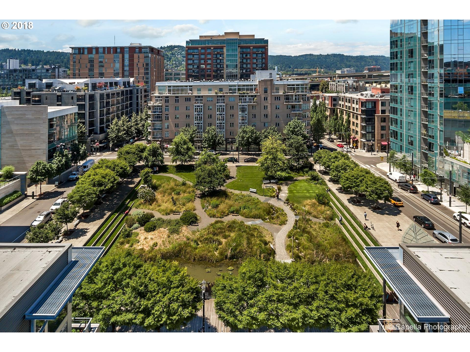 Lush green trees create serene environment, privacy and lovely view at Bridgeport condos on Tanner Springs Park.Spectacular floor plan-main living area has newly refinished Birch floors, gas fireplace, deck and eating bar and designated dining area, Master suite overlooks quiet courtyard. Guest room on opposite end of unit with murphy bed and walk-in closet. New paint/carpet.