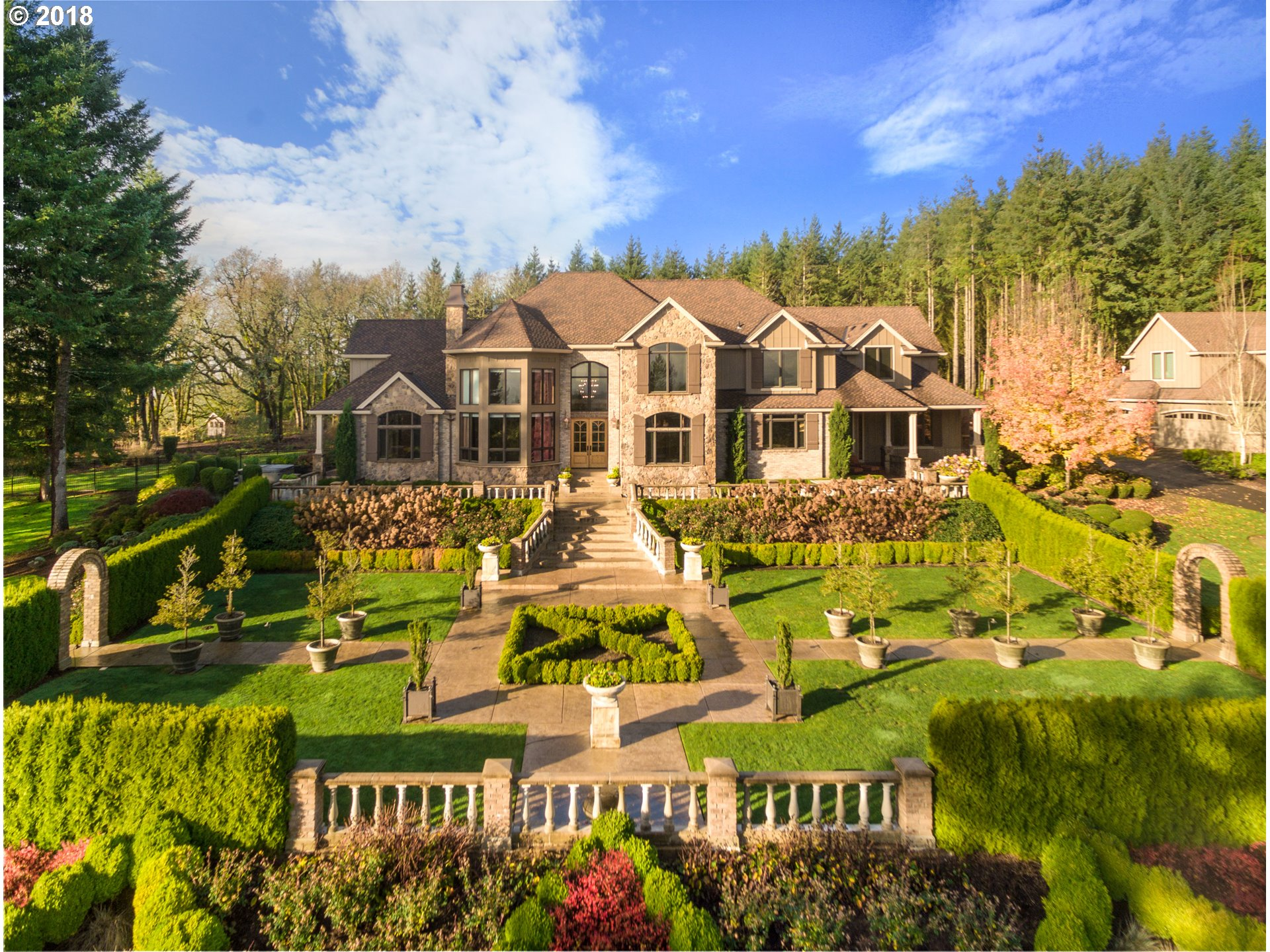 Situated on 20 acres w/panoramic views of Mt. Hood & the Willamette Valley, this 7,000+sf, 8-car garage, gated, vineyard home - is an entertainers dream! Gourmet kitchen opens to stunning family room; main level master w/private hot-tub; year-round heated/cooled, indoor/outdoor kitchen w/fireplace/TV; theatre/playroom with full wet-bar & new state of the art sound & security system. Outdoor amenities. Close to Oregon Golf Club.